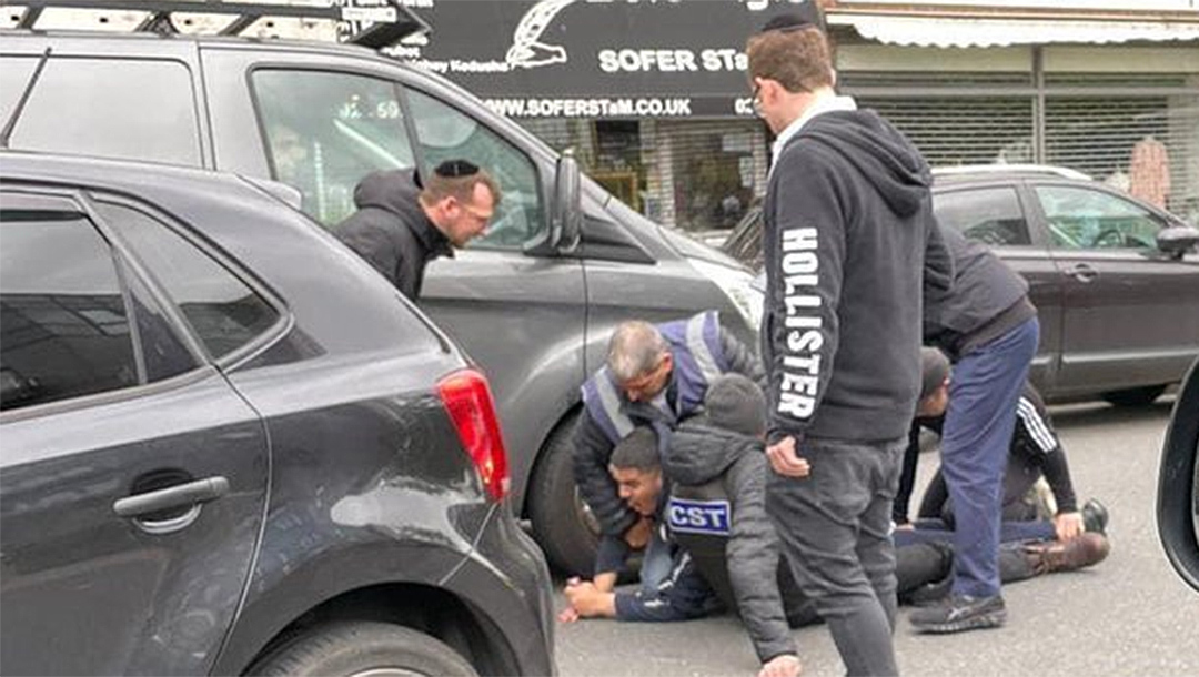 Men from the CST and Shomrim security units detaining a man whom witnesses said assaulted a Jewish man in a car in London, the UK on May 21, 2021. (Eye on Antisemitism)