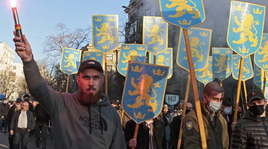 Marchers hold up the symbol of the 14th Waffen Grenadier Division of the SS in Kyiv, Ukraine on April 28, 2021. (Anna Marchenko\TASS via Getty Images)