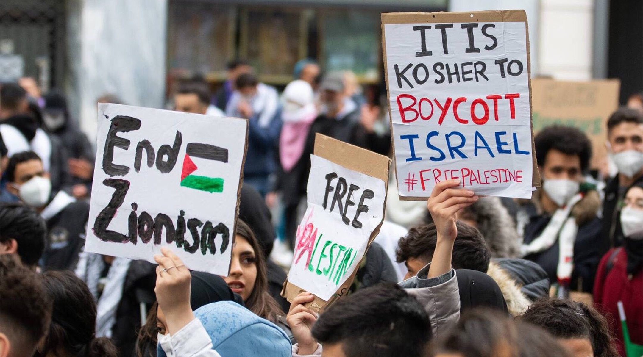 Demonstrators against Israel hold up signs at a rally in Vienna, Austria where protesters chanted in Arabic about a massacre of Jews on May 13, 2021. (Courtesy of Austrian Union of Jewish Students)
