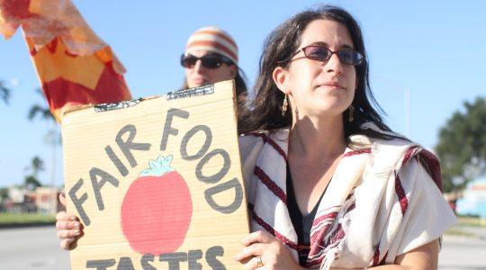 Rabbi Rachel Kahn-Troster holding a sign at a protest