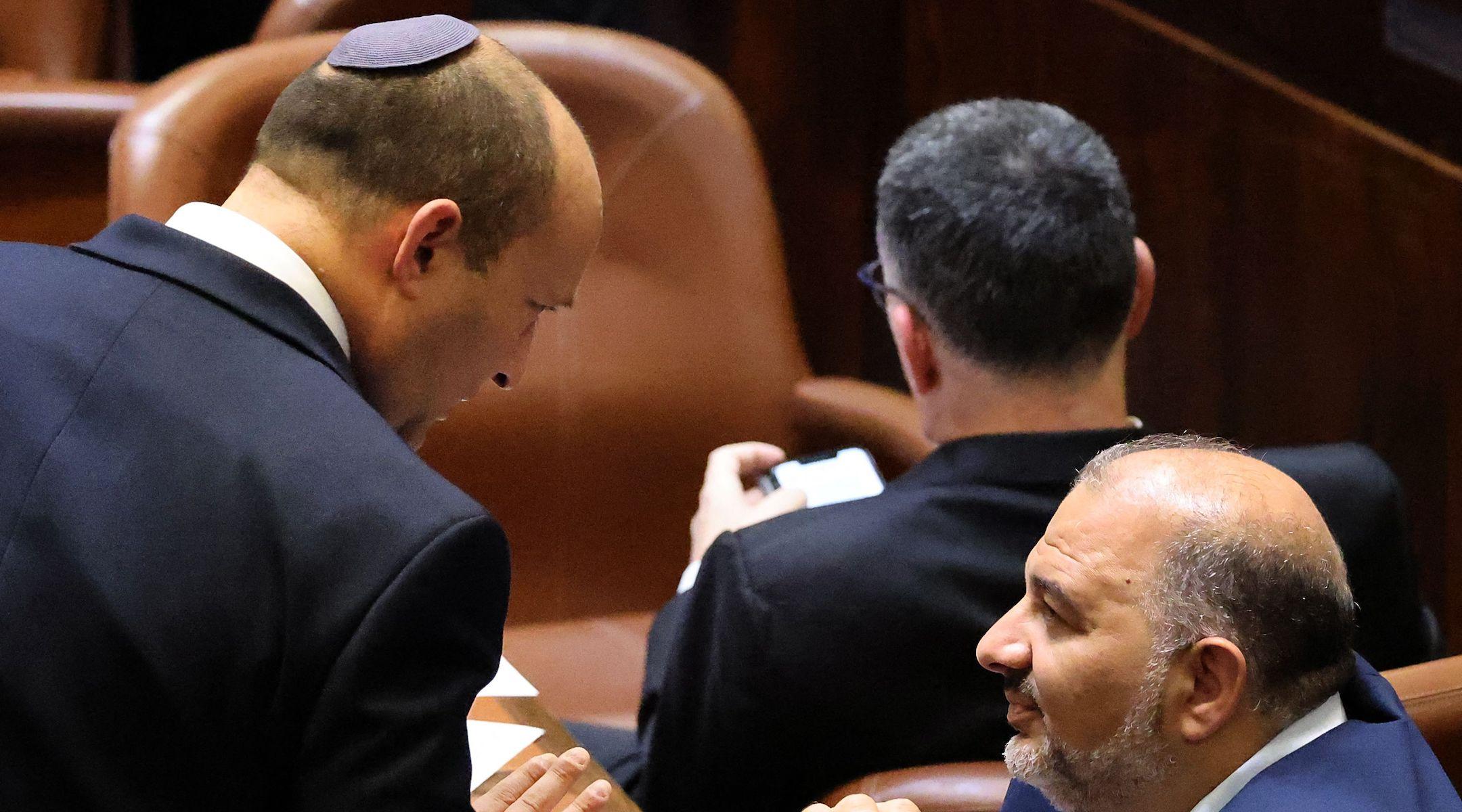 Naftali Bennett (left) speaks in Israel's Knesset with coalition partner Mansour Abbas on June 13, 2021, the day Bennett became prime minister of Israel. (Emmanuel Dunand/AFP via Getty Images)