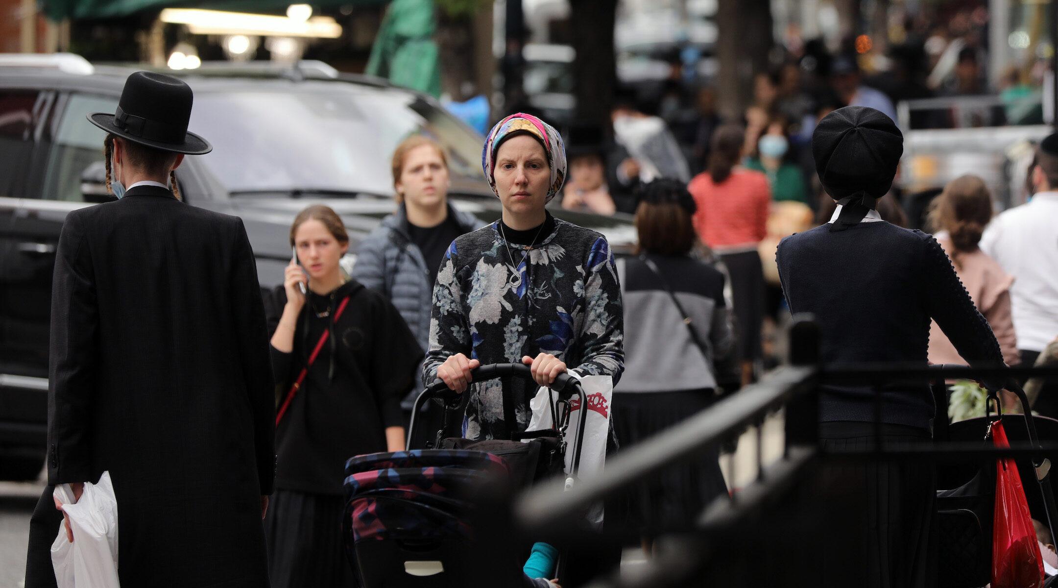 People walk through the Brooklyn neighborhood of Williamsburg in New York City