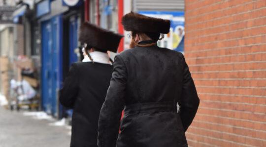 Jewish men walk in Stamford Hill, London