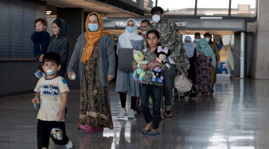 Refugees arriving at an airport; a girl clutches a Mickey Mouse doll
