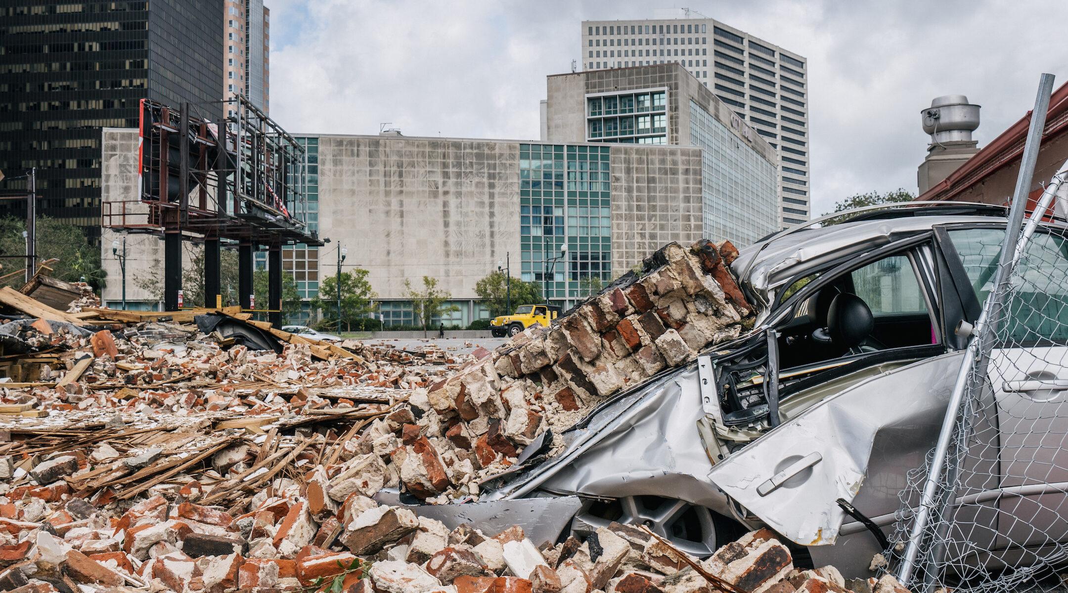 A car is seen under rubble