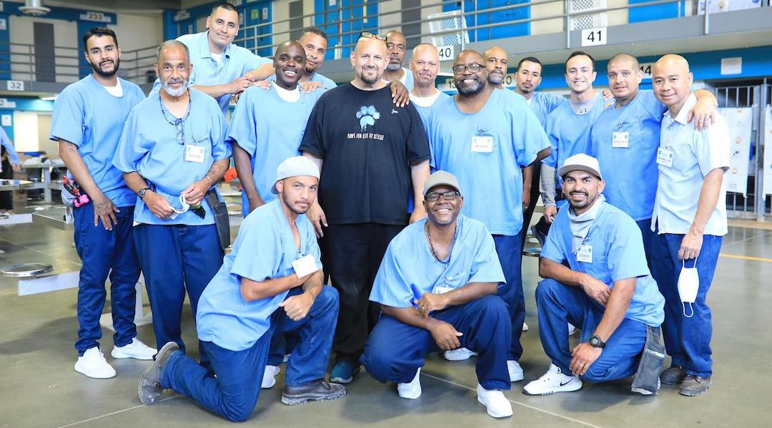 A group of incarcerated men pose for the camera around a formerly incarcerated man.