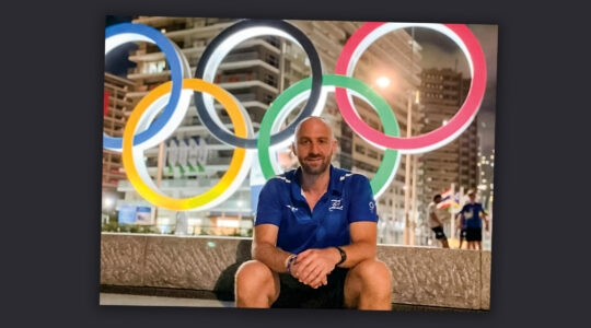 A man sitting at the Olympic Games in Tokyo, the Olympic rings behind him.