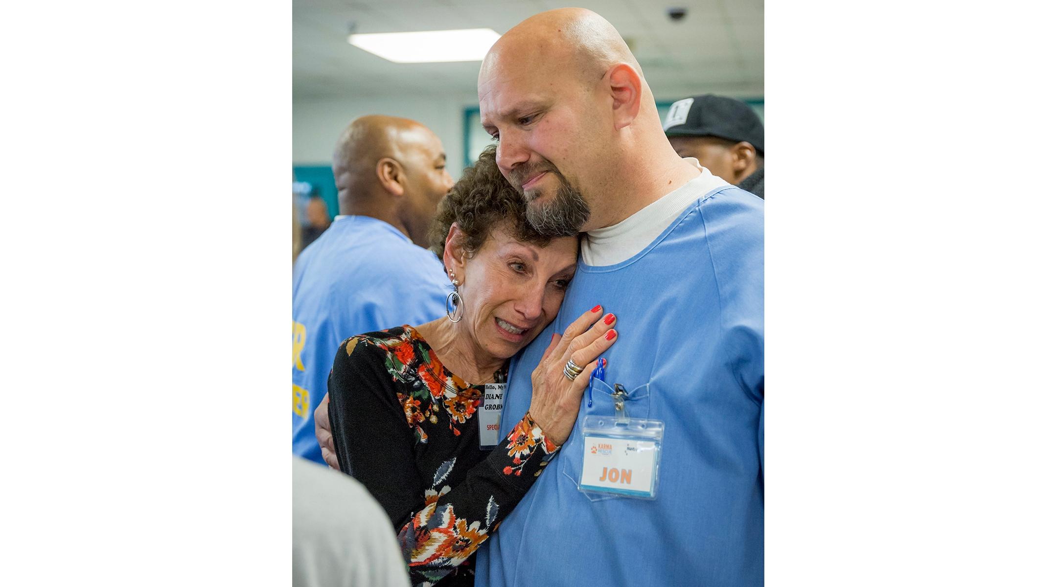 An incarcerated man hugs his mother.