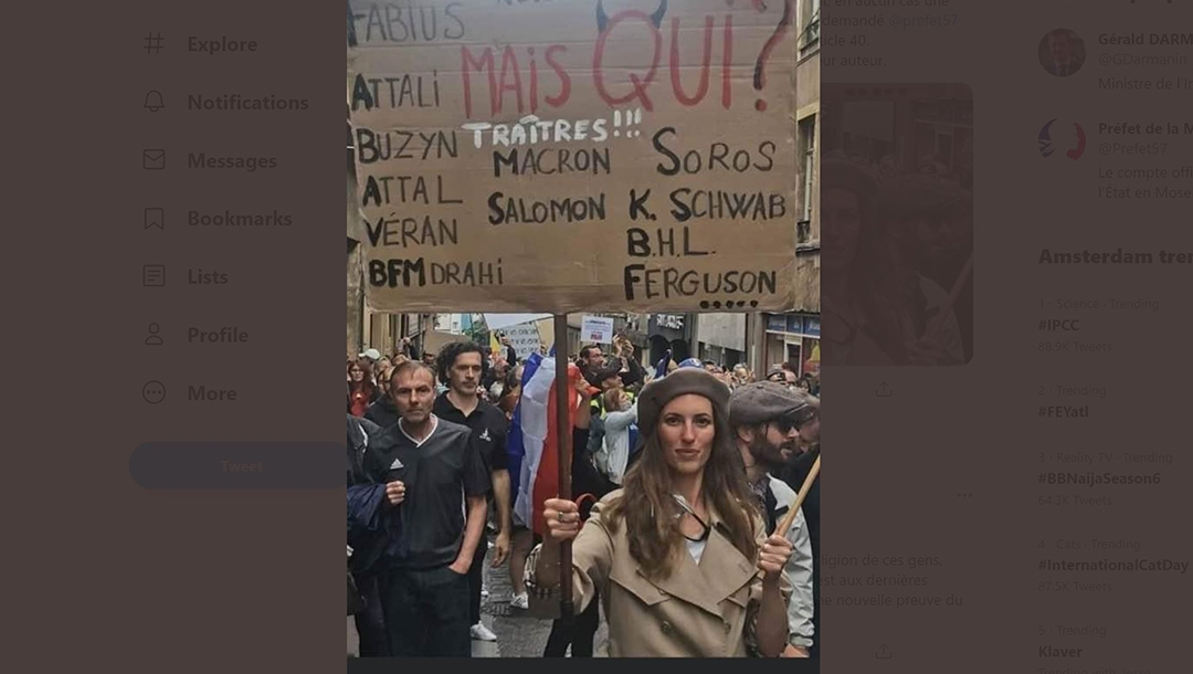 A woman holds up a placard denouncing President Emmanuel Macron and several prominent Jews denounced as traitors at a protest against COVID restrictions in Metz, France on Aug. 7, 2021. (Gérald Darmanin/Twitter)