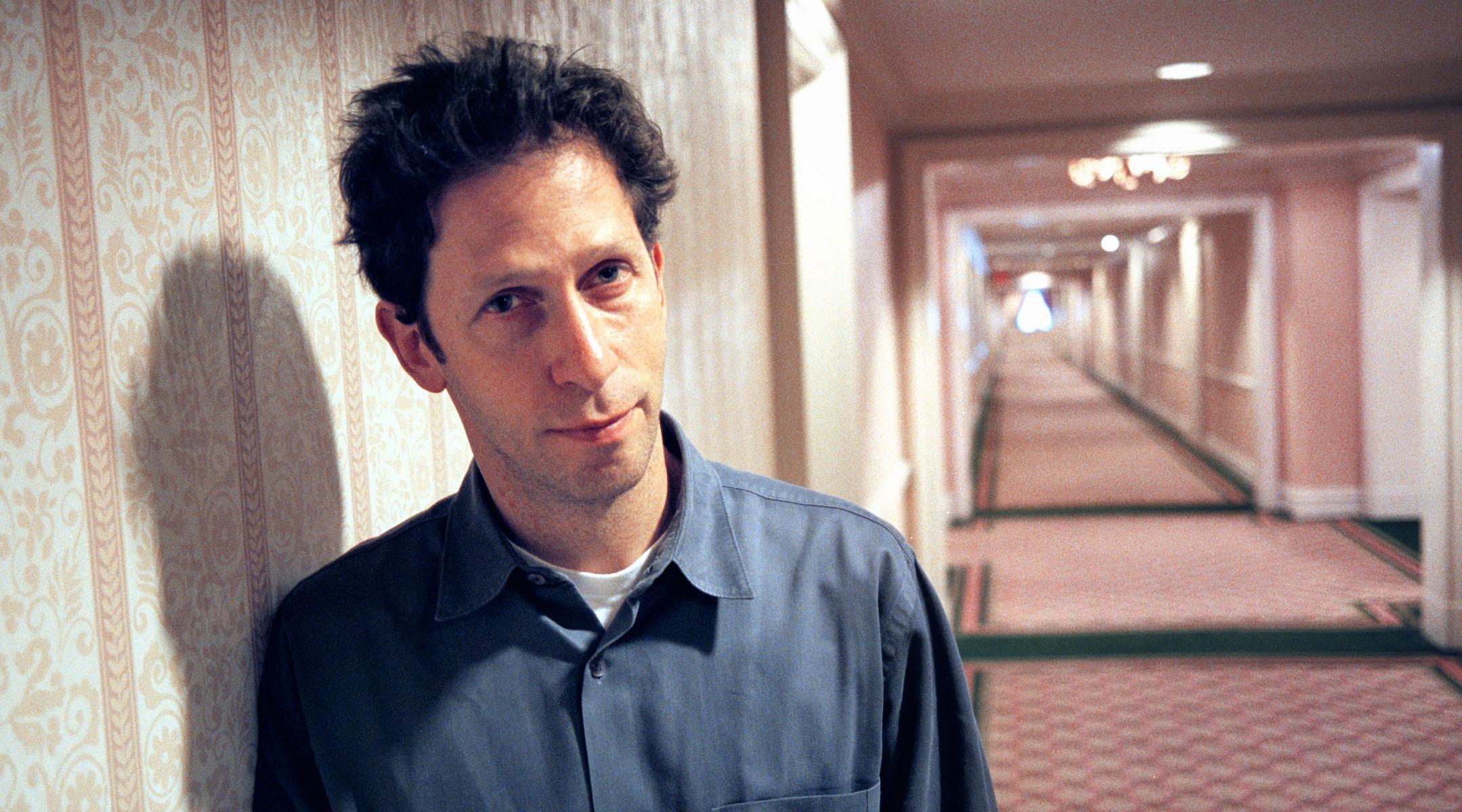 Tim Blake Nelson in a hotel hallway