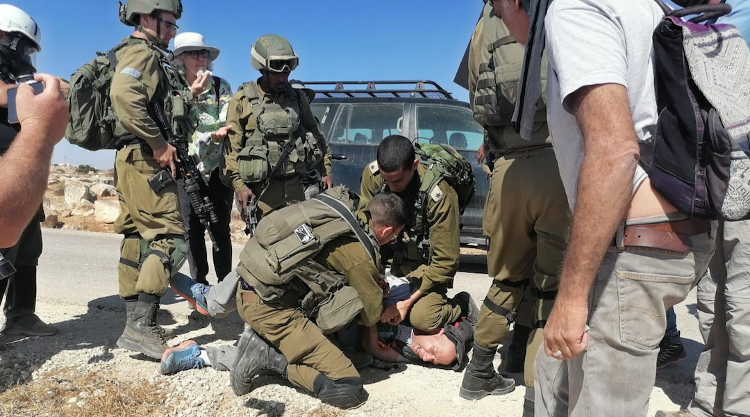 soldier kneels on the neck of an activist