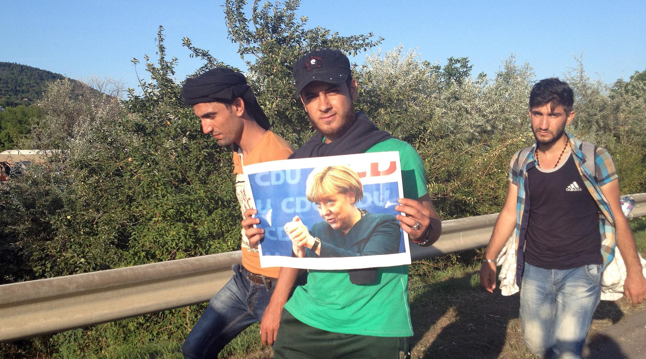 Syrian refugees carry a photograph of Angela Merkel