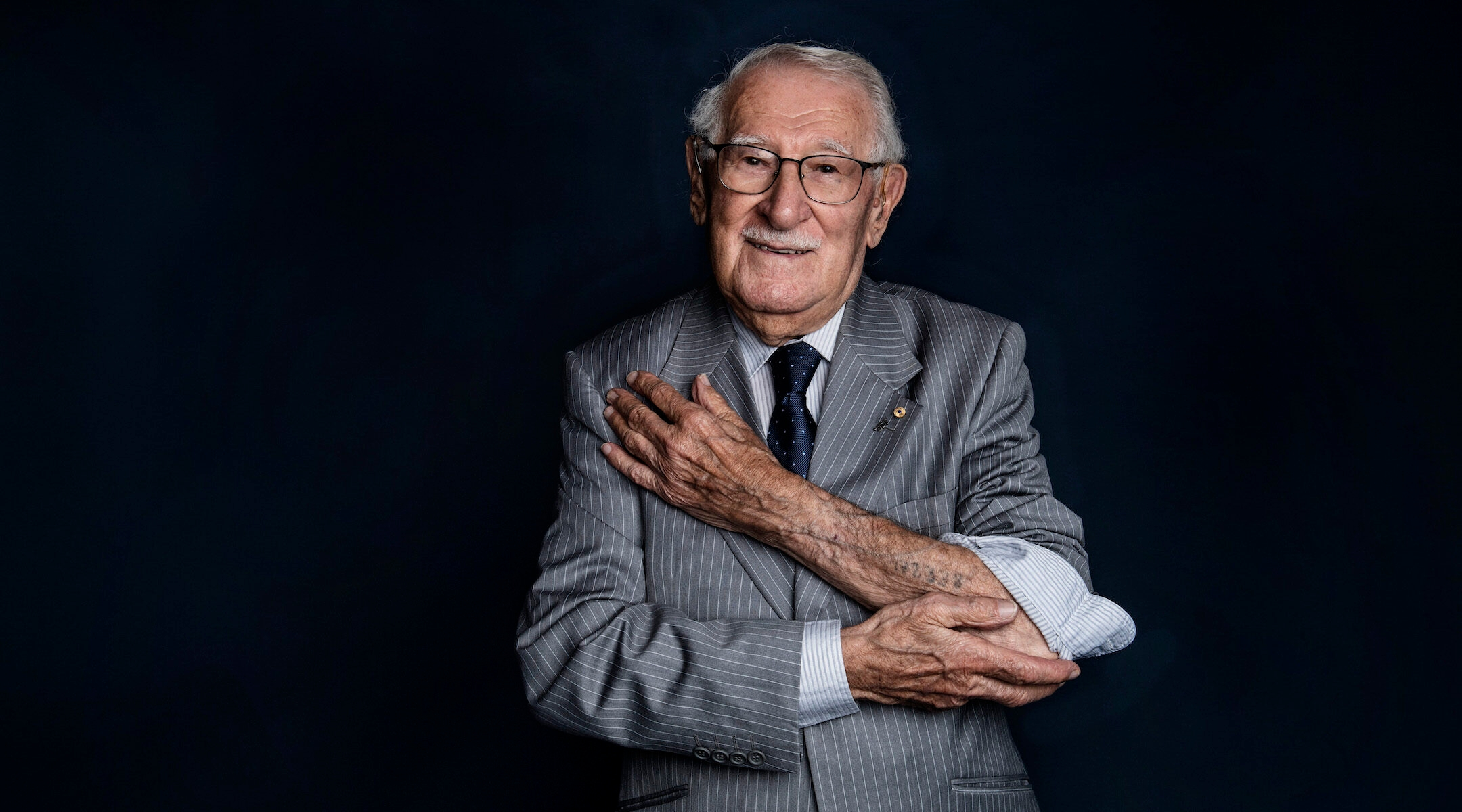 Holocaust survivor Eddie Jaku shows the concentration camp number tattoo on his left arm