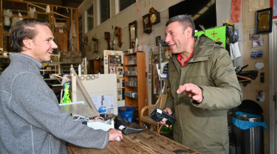 Gideon Italiaander, right, bargains with a customer at his shop in Amsterdam, the Netherlands on Oct. 11, 2021. (Cnaan Liphshiz)